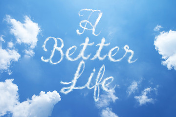 A BETTER LIFE hand cloud written word on sky background. Calligraphy style.