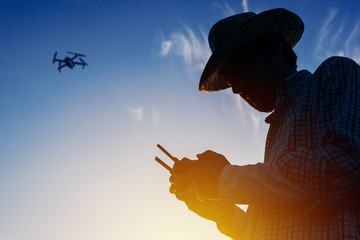 Silhouette of farmer using drone remote control