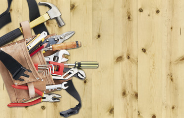 New tool belt with an assortment of new tools, laying at the side of clean fresh wood, with lots of copy space.