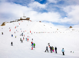 Skiers and snowboarders on the top station slope in Courchevel winter resort, France.