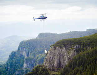 helicopter carrying goods on mountain landscape