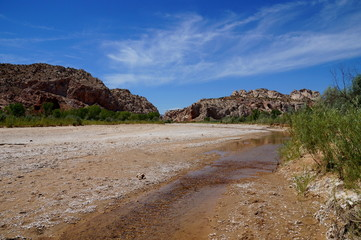 Foto auf Leinwand Fluss Rising global warming: wide river dried out to a tiny stream riverbed. Rising global temperature increases evaporation and reduces rainfall in arid areas reducing wide streams to tiny runlets.