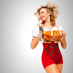 Serving with smile / Beautiful woman wearing red jumper shorts with suspenders as traditional dirndl, serving two beer mugs on grey background.