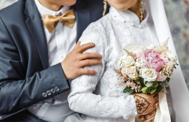 The bride and groom embrace and hold a wedding bouquet of pastel flowers, close-up