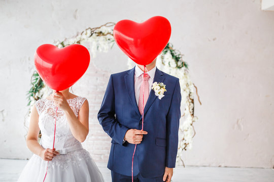 Happy groom and bride covered their faces with red balloons at wedding party indoors
