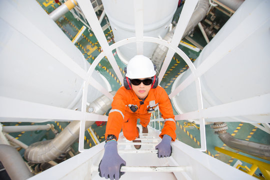 Oil and gas industry worker climb up to pressurized gas vessel for checking  oil and gas dehydration process at the top of vessel.