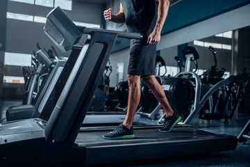 Male person workout on running exercise machine