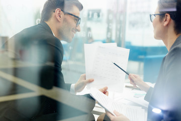 Woman pointing at paper with financial data while talking to colleague