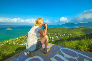 Travel photographer takes shot of Lanikai Beach and Mokulua Islands in Oahu East shore, Hawaii, USA. Nature photographer taking pictures outdoors during hawaiian hiking Lanikai Pillbox Hike.
