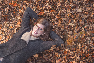 Smiling young woman lying on brown leaves in Autumn