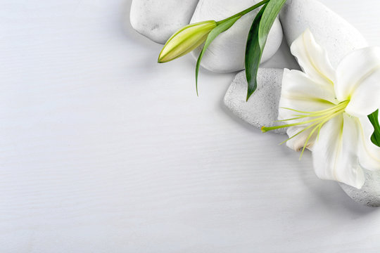 Spa stones and beautiful lily on white wooden background