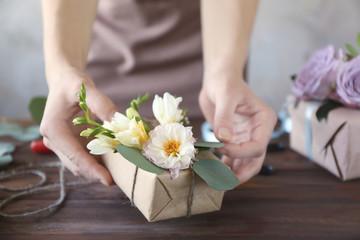Florist decorating box with flowers, closeup