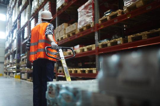 Warehouse forklifter pulling machine while walking along shelves