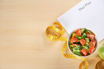 Diet plan, salad and measuring tape on wooden table