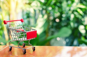 mini supermarket shopping cart on blurred green nature background with sunlight effect, holiday sale and shopping concept, selective focus, copy space