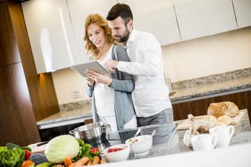 Man helping his girlfriend cooking in modern kitchen
