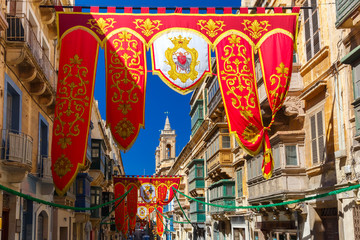 Festively decorated street with banners for St Augustine Feast in the old town of Valletta, Malta. Flaming, arrow pierced heart - symbol of St Augustine