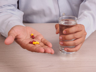 man hands with pills and glass of water