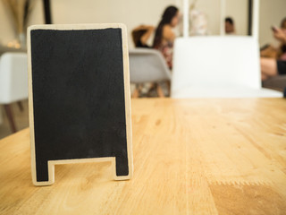 Blank chalkboard standing on wood table at coffee shop, space for text, mock up.