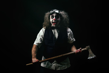 Portrait d'un clown criant, une hache ensanglanté dans ses mains