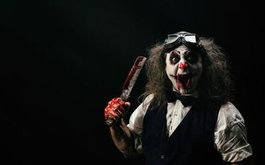 Portrait d'un clown criant, un couteau ensanglanté dans sa main