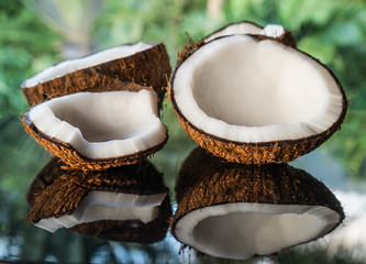 Closeup of coconuts on the black glass table isolated over blurred palm trees background