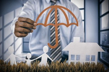 Composite image of insurer protecting family by a red umbrella