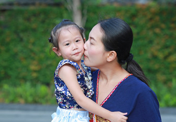 Portrait of mother and daughter in traditional songkran festival dress kissing.