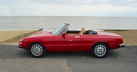 Classic Red Italian Sports  Convertible  Motor Car Parked on Seafront Promenade.