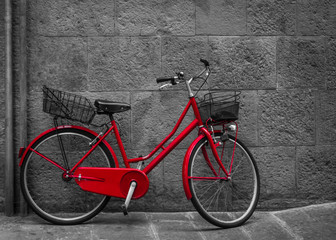 Classical red bicycle on stone wall