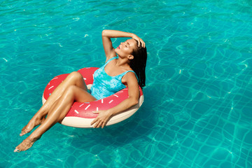 Beautiful woman and inflatable swim ring in shape of donut