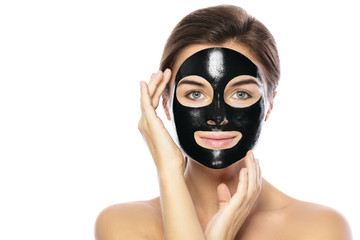 Woman with purifying black mask on her face