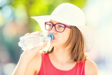 Young girl drinking fresh water on a hot summer day.