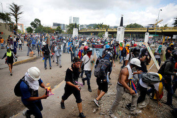 Demonstrators clash with riot security forces while rallying against Venezuela's President Nicolas Maduro in Caracas