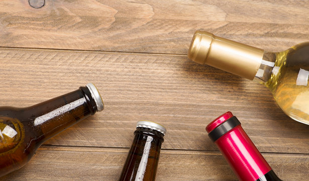 Top view of two beer bottles and a white wine on wooden table. Copy space.