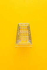 top view of shopping trolley on yellow background with some copy space