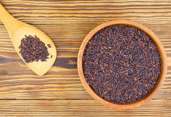 Raw black rice in bowl on  wooden background