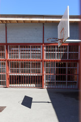 Basketball court surrounded by metal bars in city