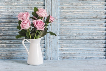 Pink roses in white enamel jug on a blue rustic background. Free space for text. Vintage style