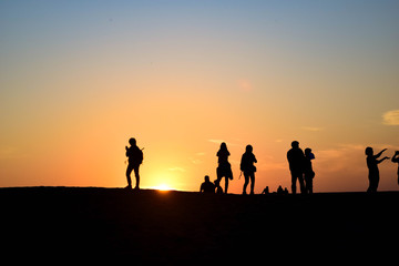 People in desert sunset