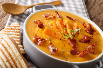Sweet potato soup with bacon and herbs in a pan macro. horizontal