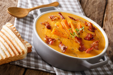 Healthy sweet potato cream soup with bacon and herbs in a saucepan and toast closeup. horizontal