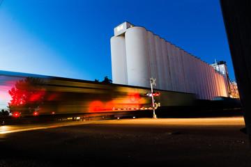 Train Moving Near Grain Silos