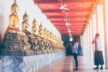 Young woman traveler with backpack respecting or pray at many buddha statue in Wat Pho at Bangkok Thailand