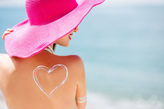 Back view on a beautiful woman in pink hat with sunscreen heart shape on her shoulder having a sunbath on the beach