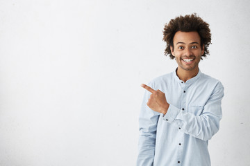 Horizontal portrait of dark-skinned handsome man having broad smile wearing formal white shirt posing against white background pointing with index finger at white copy space for your advertisment