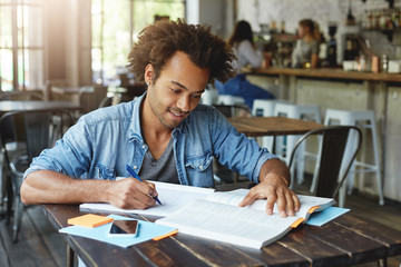 Stylish hipster guy with African hairstyle wearing denim shirt sitting in cafeteria working with books writing some notes preparing for lessons. Hard-working student being busy with studying