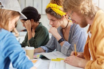 Youth, education and friendship concept. Group of clever creativ students sitting together in canteen surrounded with books and notebooks drinking coffee having concentrated and serious look