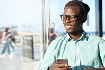 People, urban lifestyle, technology and communication concept. Attractive young Afro American hipster with broad charismatic smile checking e-mail or shopping online on his modern electronic gadget