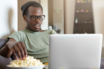 Headshot of dark-skinned hipster male in big shades sitting at home watching his favourite serial eatting popcorn looking with excitement into screen of his computer. Modern technologies and leisure